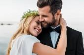 Fotografie milující svatební pár v obleku a bílé šaty objímání na pláži