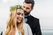 Fotografie portrait of handsome groom in suit hugging attractive bride on beach