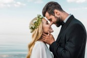 Fotografie happy wedding couple in suit and white dress touching with noses on beach