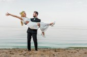 Fotografie handsome groom in suit holding attractive smiling bride in white dress on beach