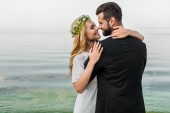 attractive bride in wreath and groom in suit cuddling on beach and touching with noses