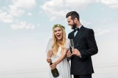 happy bride in white dress opening champagne bottle on beach