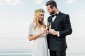 Fotografie smiling wedding couple clinking with glasses of champagne on beach