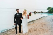 wedding couple holding hands and walking on sandy ocean beach