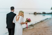 Fotografie back view of wedding couple with bouquet walking on beach