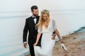 happy wedding couple hugging and walking on beach, bride holding high heels in hand