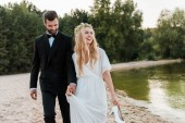 Fotografie wedding couple holding hands and walking on beach, laughing bride holding high heels in hand