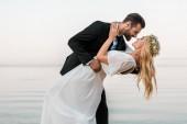 milující svatební pár políbí na pláži