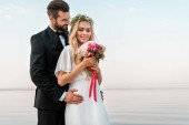 Fotografie groom hugging bride and she holding wedding bouquet on beach