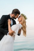 affectionate romantic wedding couple going to kiss on beach