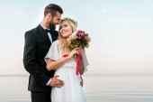 groom hugging smiling bride and she holding wedding bouquet on beach