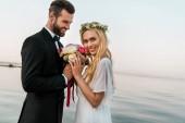 Fotografie boční pohled na svatební pár stojící s kyticí na pláži, usmíval se nevěsta při pohledu na fotoaparát