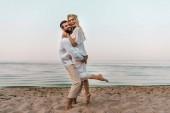 Fotografia sposo che abbraccia ridendo bella sposa sulla spiaggia