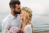 Fotografie side view of handsome groom kissing attractive bride forehead on beach