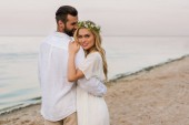 Fotografie groom hugging attractive bride in wreath and she looking at camera on beach