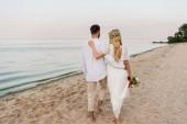 zadní pohled na nevěsta s ženich objímání a chůze po pláži a svatební kytice