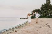 happy bride running with wedding bouquet, groom grimacing on beach