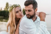 Fotografie portrait of beautiful bride in wreath and handsome groom on beach