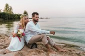 Fotografie handsome groom and bride with wedding bouquet sitting on log on beach