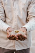 Fotografie cropped image of groom holding wedding rings with sand in hands on beach