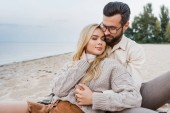 Fotografie affectionate couple in autumn outfit sitting and hugging on beach