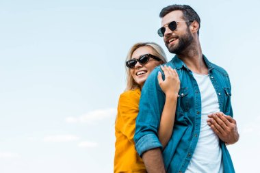 low angle view of smiling girlfriend hugging boyfriend against blue sky