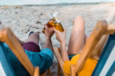 Cropped image of couple sitting on sun loungers and clinking with glass bottles of beer on sandy beach stock vector