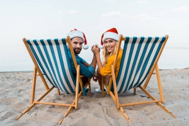 Couple in santa hats sitting on sun loungers, holding hands and looking at camera on beach stock vector