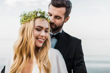 portrait of handsome groom in suit hugging attractive bride on beach