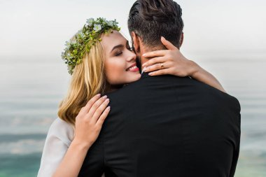 attractive bride with closed eyes and groom in suit hugging on beach
