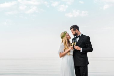 affectionate wedding couple clinking with glasses of champagne on beach