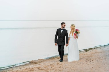 wedding couple holding hands, walking and looking at each other on beach