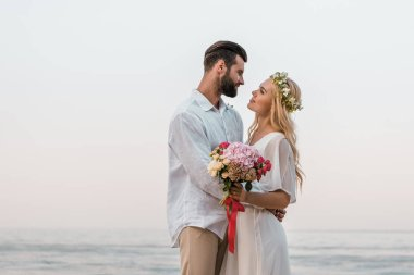 side view of affectionate bride and groom hugging and looking at each other on beach