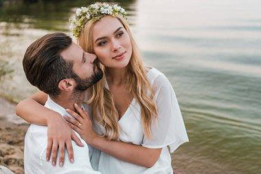 attractive bride in wreath hugging groom on beach