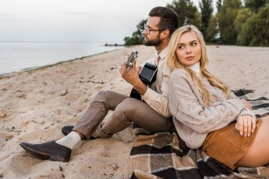 handsome boyfriend in autumn outfit playing acoustic guitar for girlfriend during date on beach