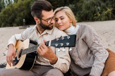 handsome boyfriend in autumn outfit playing acoustic guitar for attractive girlfriend on beach