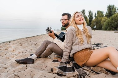 handsome boyfriend in autumn outfit playing acoustic guitar for smiling girlfriend on beach