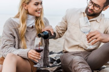 boyfriend in autumn outfit pouring red wine into glasses on beach