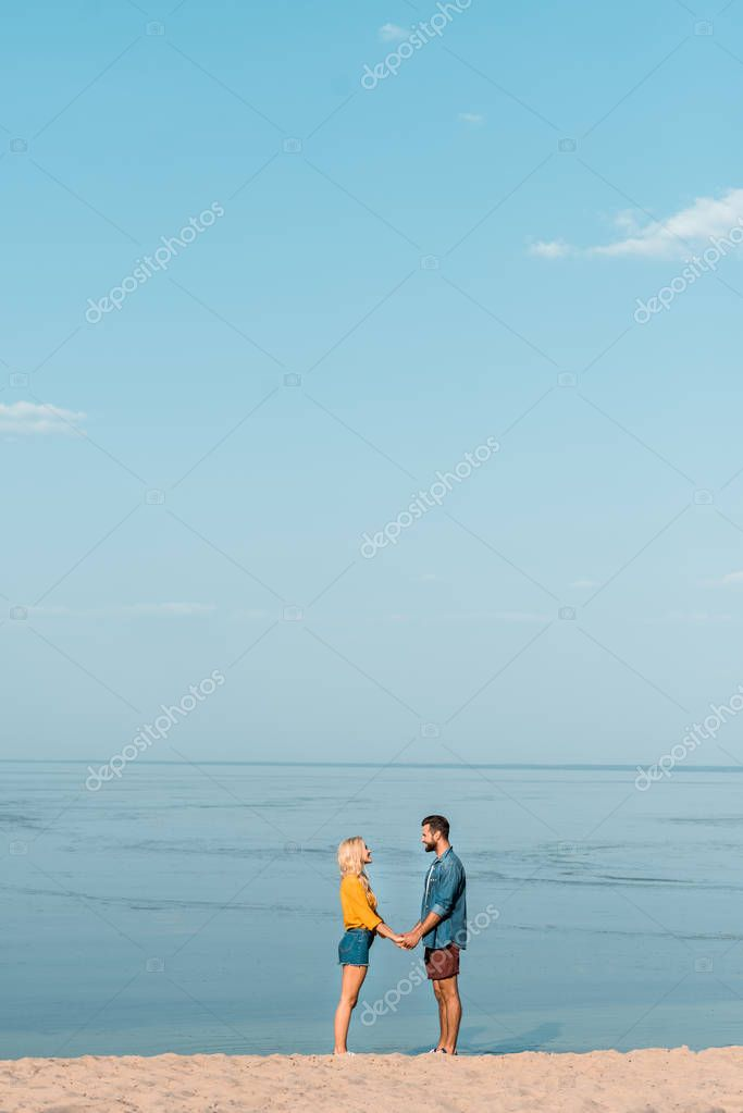couple holding hands and looking at each other on beach