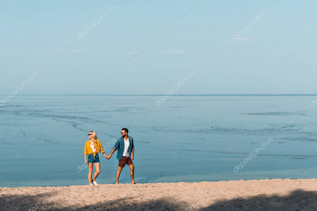 couple holding hands and walking on sandy beach