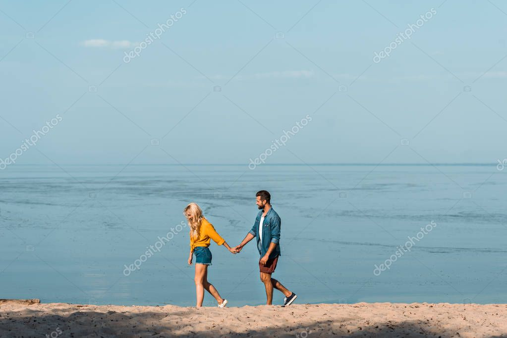 girlfriend and boyfriend holding hands and walking on sandy beach