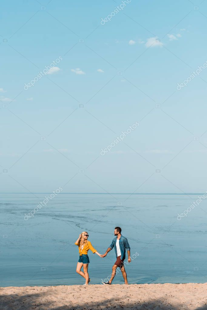 girlfriend and boyfriend holding hands and walking on sandy seashore