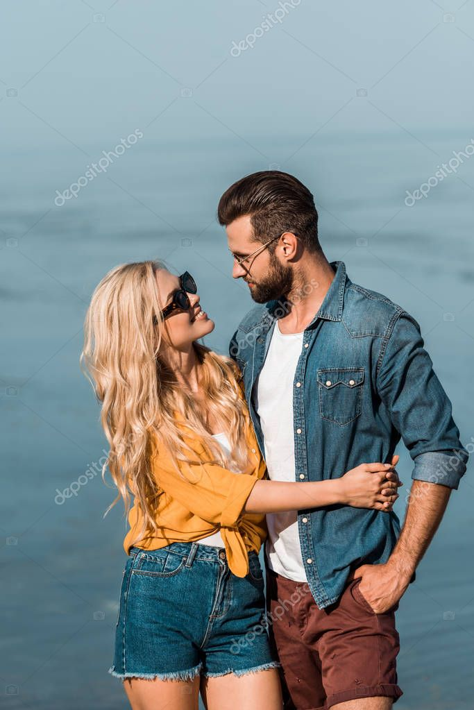 couple in sunglasses hugging and looking at each other near sea