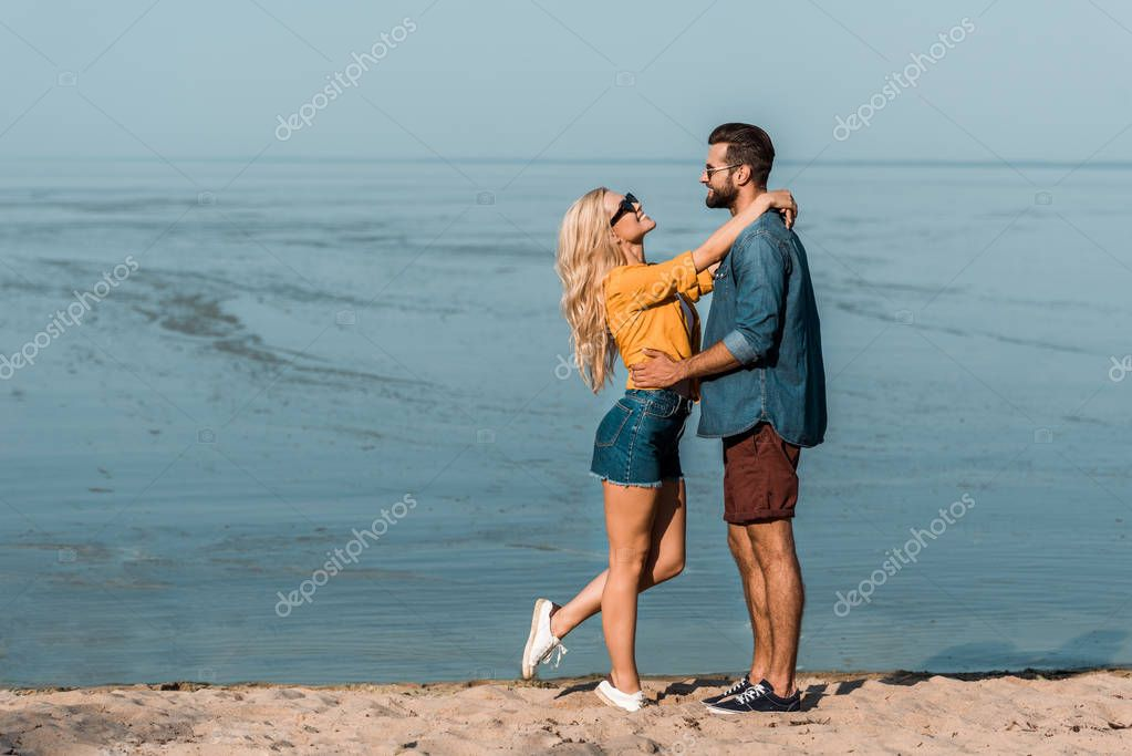 couple in sunglasses cuddling and looking at each other on beach