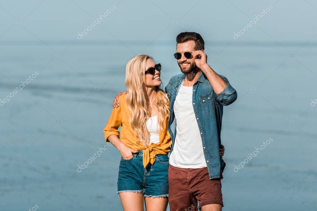 smiling couple in sunglasses standing near ocean