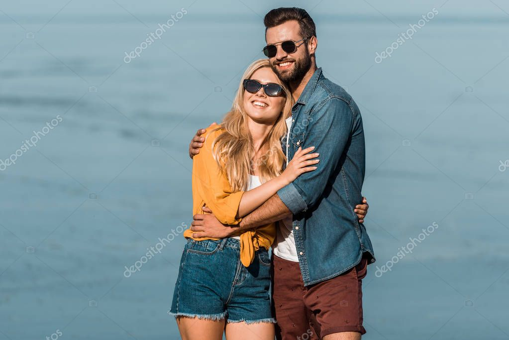 smiling couple in sunglasses hugging and standing near ocean