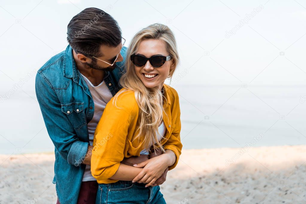 boyfriend hugging happy girlfriend on beach