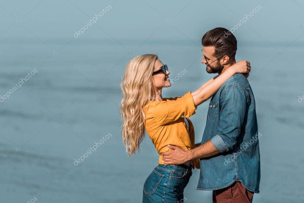 couple in sunglasses cuddling and looking at each other near ocean