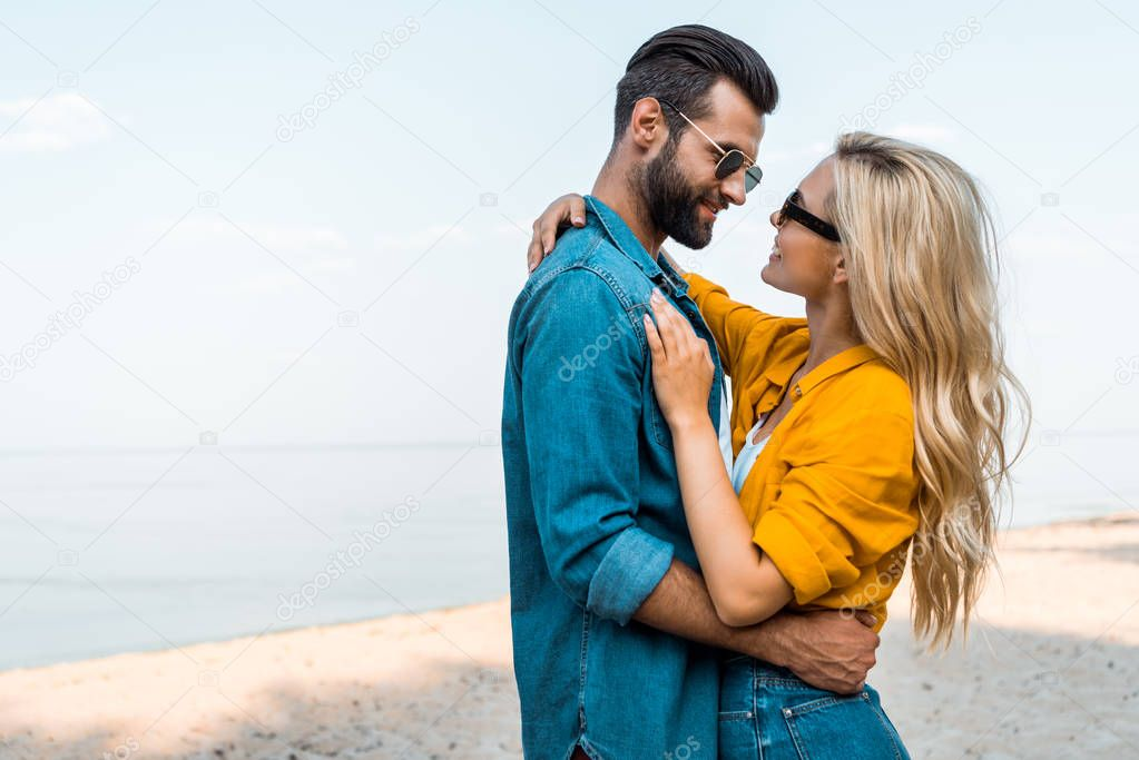 side view of couple in sunglasses hugging and looking at each other near ocean