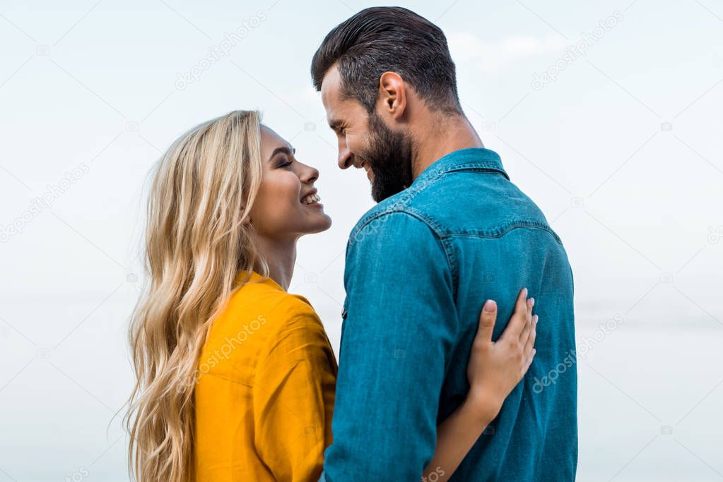 side view of smiling couple hugging and looking at each other against blue sky